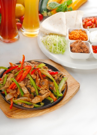 original fajita sizzling smoking hot served on iron plate ,with selection of beer and fresh vegetables on background ,MORE DELICIOUS FOOD ON PORTFOLIO Stock Photo - 11594221