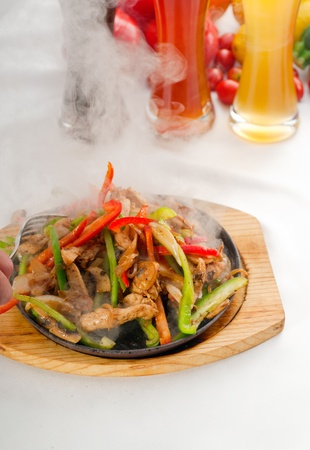 sizzling: original fajita sizzling smoking hot served on iron plate ,with selection of beer and fresh vegetables on background ,MORE DELICIOUS FOOD ON PORTFOLIO Stock Photo