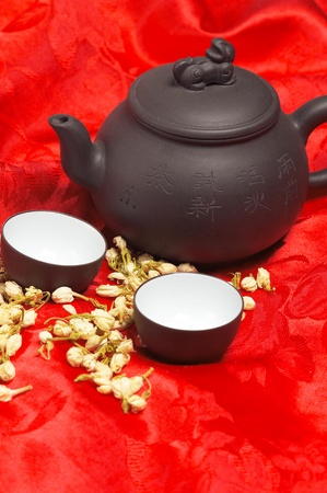 jasmine tea dry flowers,pot and two cups ,over red silk tablecloth