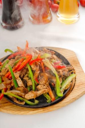 Original fajita sizzling Akt serviert auf heißer Platte, mit einer Auswahl an Bier und frischem Gemüse