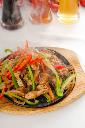 original fajita sizzling smoking hot served on iron plate ,with selection of beer and fresh vegetables  Stock Photo