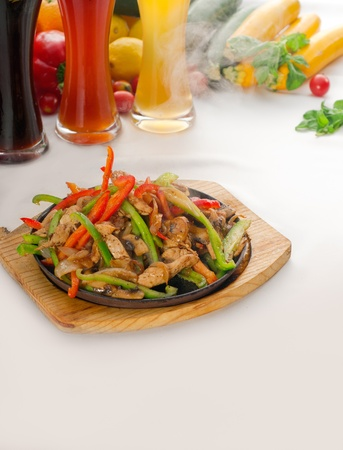 original fajita sizzling smoking hot served on iron plate ,with selection of beer and fresh vegetables