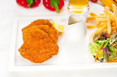 classic breaded Milanese veal cutlets with french fries and vegetables on background  photo