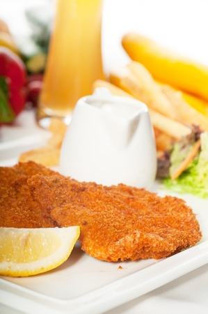 classic breaded Milanese veal cutlets with french fries , vegetables and glass of lager beer on background   photo