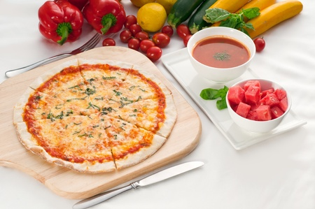 Italian original thin crust pizza Margherita with gazpacho soup and watermelon on side,and vegetables on background photo