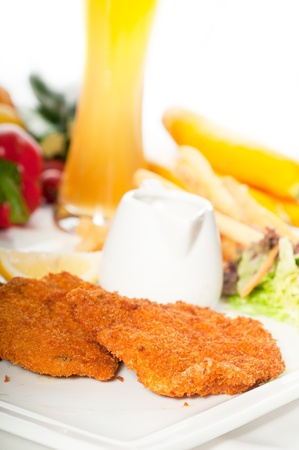classic breaded Milanese veal cutlets with french fries , vegetables and glass of lager beer on background. photo