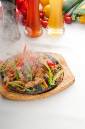 original fajita sizzling smoking hot served on iron plate ,with selection of beer and fresh vegetables on background. photo