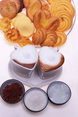 valentine day heart shaped espresso coffee cappuccino cups with assortment of pastry mignon  and white brown and rock sugar over white photo