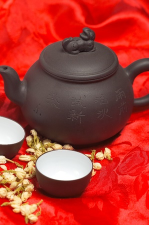 jasmine tea dry flowers,pot and two cups ,over red silk tablecloth photo