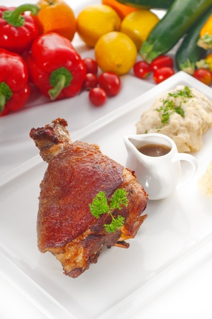 original German BBQ pork  knuckle served with mashed potatoes and  sauerkraut ,fresh vegetables on background,MORE DELICIOUS FOOD ON PORTFOLIO photo