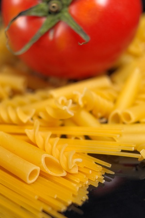 Italian pasta selection with fresh tomato over black closeup DOF photo