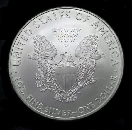 antique coins: American silver eagle dollar coin over black