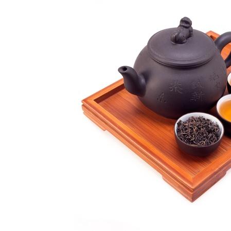 Chinesischer grüner Tee Tontopf und Tassen auf Bambusholz Fach isoliert über weiß Standard-Bild