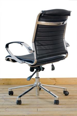 modernen Bürostuhl aus schwarzem Leder auf Holz Boden auf weißem Hintergrund