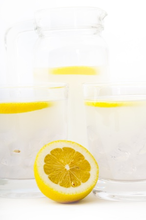 fresh lemonade drink with lemon slice closeup and pitcher carafe photo