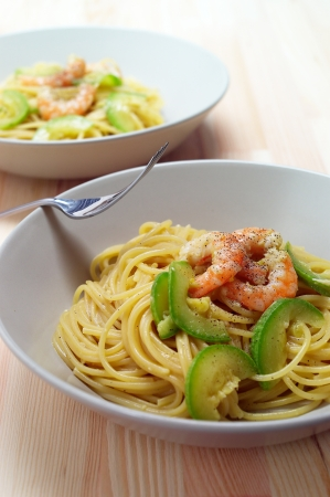 spaghetti pasta with fresh shrimps and zucchini sauce over wood table photo