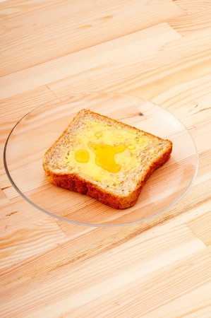 slice of whole grain bread with butter and honey photo