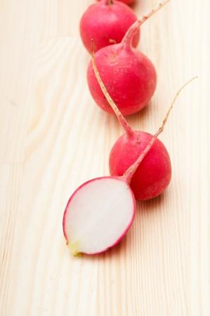 raddish: fresh red raw  raddish over pine wood table closeup