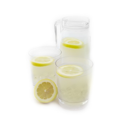 fresh lemonade drink with lemon slice closeup and pitcher carafe isolated photo