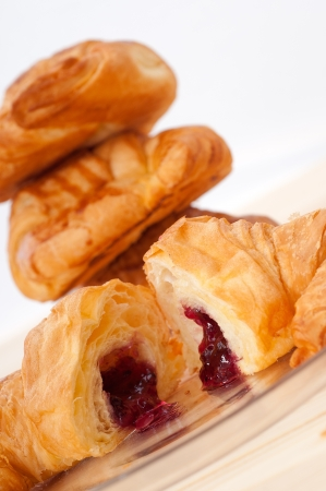 fresh baked croissant French brioche filled with berries jam photo