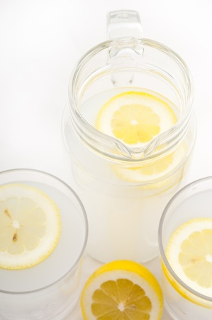 fresh lemonade, drink with lemon slice closeup and pitcher carafe photo