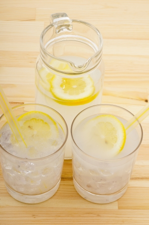 fresh lemonade drink with lemon slice closeup and pitcher carafe over pinewood table photo