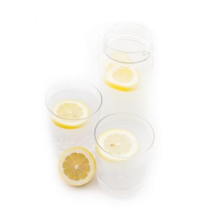 fresh lemonade ,drink with lemon slice closeup and pitcher carafe isolated photo