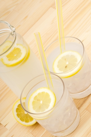 fresh lemonade drink with lemon slice closeup and pitcher carafe over pinewood table Stock Photo - 15226460