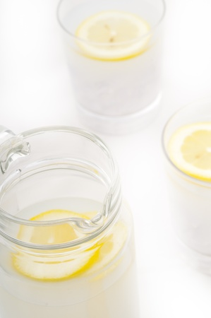 fresh lemonade drink with lemon slice closeup and pitcher carafe Stock Photo - 15279526
