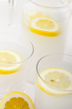 fresh lemonade drink with lemon slice closeup and pitcher carafe Stock Photo - 15377899