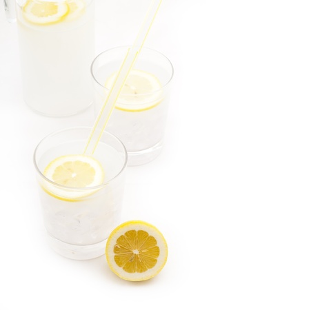 fresh lemonade drink with lemon slice closeup and pitcher carafe isolated Stock Photo - 16216808