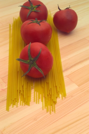 fresh tomato and raw spaghetti pasta over pine wood table Stock Photo - 16216847