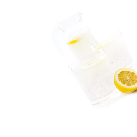 fresh lemonade drink with lemon slice closeup and pitcher carafe isolated Stock Photo - 16453102