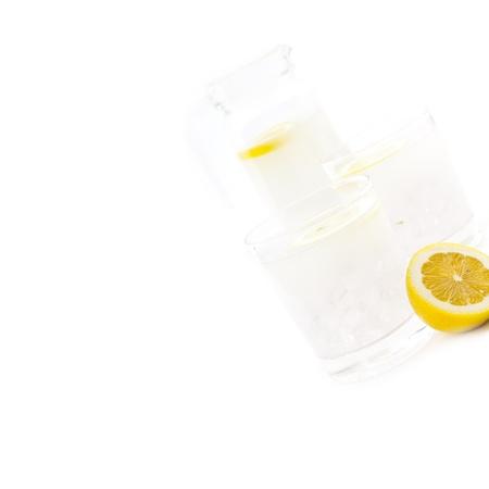 fresh lemonade drink with lemon slice closeup and pitcher carafe isolated Stock Photo - 16453102