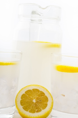 fresh lemonade drink with lemon slice closeup and pitcher carafe Stock Photo - 16453104