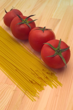 fresh tomato and raw spaghetti pasta over pine wood table Stock Photo - 16453108