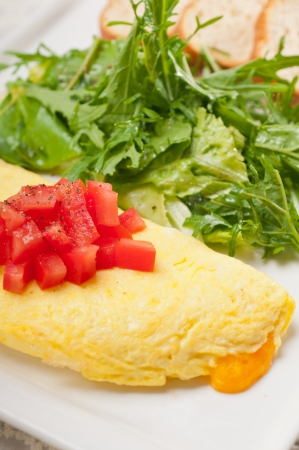 home made omelette with cheese tomato and rucola rocket salad arugola Stock Photo