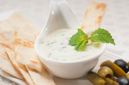 fresh Greek Tzatziki yogurt dip and pita bread and pickels