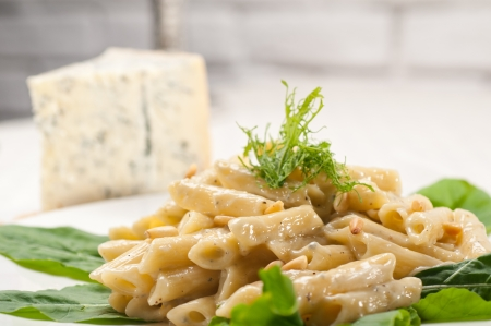 Italian traditional pasta penne gorgonzola and pine nuts Stock Photo