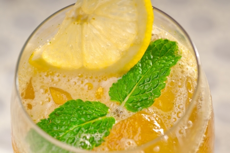 refreshing Ice tea closeup macro with lemon and mint leaves photo