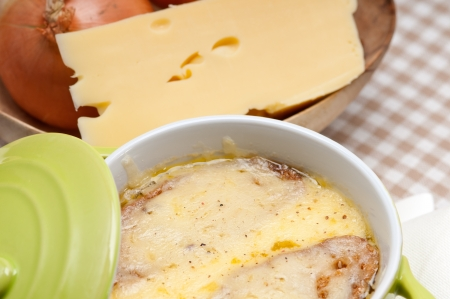 oinion soup on clay pot with melted cheese and bread on top photo