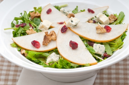 Fresh pears arugula gorgonzola cheese salad with cranberry and walnuts photo