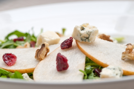 Fresh pears arugula gorgonzola cheese salad with cranberry and walnuts photo