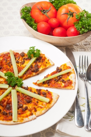 fresh baked Turkish beef pizza with cucumber on top photo