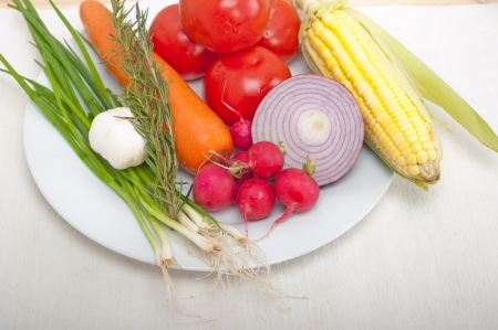 fresh vegetables and herbs on a plate cooking raw ingredients on kitchen photo