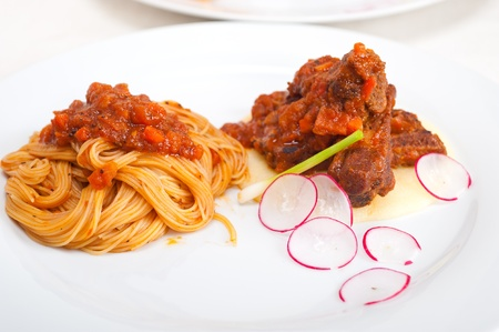 traditional Italian spaghetti pasta with pork ribbs sauce served on polenta bed photo