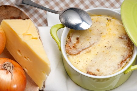 onion soup on clay pot with melted cheese and bread on top photo
