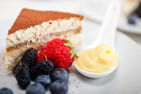 classic Italian tiramisu dessert with berries and custartd pastry cream on side