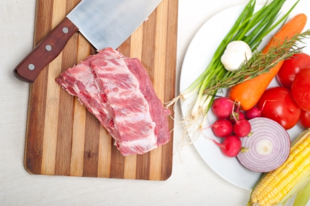 chopping fresh pork ribs with vegetables and herbs ready to cook Stock Photo - 19016813