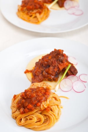 traditional Italian spaghetti pasta with pork ribbs sauce served on polenta bed Stock Photo - 19016822